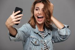 Szczęśliwa ładna brunetki kobieta dotyka jej włosy podczas gdy brać selfi obraz stock