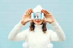 Szczęśliwa ładna dziewczyna bierze fotografii jaźni portret na smartphone nad błękitnym tłem w zimie dziającej odziewa zdjęcie stock