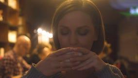 Szczęśliwa ładna kobieta z filiżanką herbata w rękach cieszy się smak gorący napój, kawiarnia zbiory