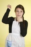 Szczęśliwa ładna młoda dziewczyna jest ubranym kulinarnego fartucha Fotografia Stock