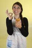 Szczęśliwa ładna młoda dziewczyna jest ubranym kulinarnego fartucha Obraz Stock