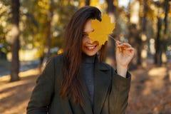 Szczęśliwa ładna młoda kobieta z uśmiechem zakrywa jej twarz z złotym żółtym jesień liściem i chodzi w parku obrazy stock