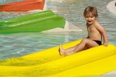 Szczęśliwa śliczna chłopiec ono ślizga się od żółtego waterslide Fotografia Stock