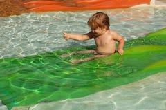 Szczęśliwa śliczna chłopiec ono ślizga się od zielonego waterslide Obrazy Stock