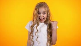 Szczęśliwa śliczna dziewczyna robi tak gestowi, zdziwionemu z dobrym rezultatem, reklama zdjęcie wideo