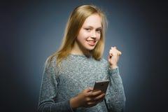 Szczęśliwa śliczna dziewczyna z telefonem komórkowym Odizolowywający na szarość fotografia royalty free