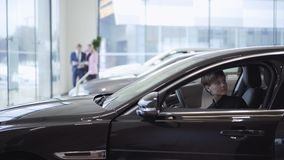 Szczęśliwa śliczna młoda dziewczyna z ciemnym włosy i krótkim włosy w pasażerskim przedziale nowy samochód Pomyślna kobieta egzam zdjęcie wideo