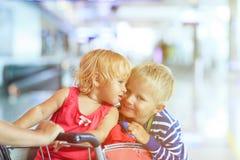 Szczęśliwa śliczna mała dziewczynka i chłopiec przy lotniskiem na bagażu furmanimy fotografia royalty free