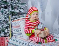 Szczęśliwa śliczna mała dziewczynka siedzi w dekorującym nowego roku pokoju w domu ubierał w pasiastych piżamach Obraz Stock