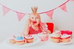 Szczęśliwa śliczna mała dziewczynka z cukierkami przy przyjęciem urodzinowym zdjęcie stock