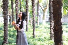 Szczęśliwa śliczna urocza piękna młodej dziewczyny szkoły średniej studenta collegu uściśnięcia uścisku natura je owocowej pomara Fotografia Stock