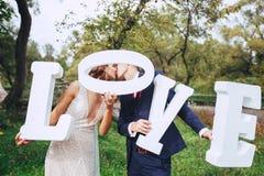 Szczęśliwa ślub para trzyma dużych białych całować i listy miłosnych fotografia stock