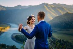 Szczęśliwa ślub para zostaje nad pięknym krajobrazem z górami zdjęcie royalty free