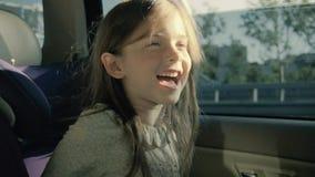 Szczęśliwa śmieszna dziewczyna w samochodzie Mała dziewczynka patrzeje przez okno w tylnym siedzeniu zdjęcie wideo