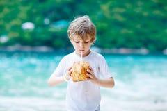 Szczęśliwa śmieszna mała preschool dzieciaka chłopiec pije kokosowego sok na ocean plaży dziecko bawić się na rodzinnych wakacjac obrazy royalty free