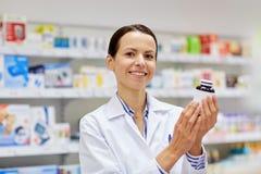 Szczęśliwa żeńska farmaceuta z leka słojem przy apteką obraz royalty free