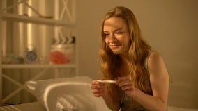 Szczęśliwa żeńska mienie ciążowego testa ręka, planowanie rodziny, macierzyński podniecenie zdjęcie wideo