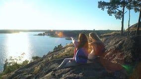 Szczęśliwa Żeńska para Pije szampana na Wysokiej skale w świetle słonecznym zbiory wideo