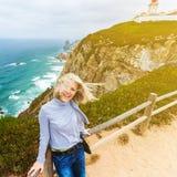 Szczęśliwa żeńska turystyczna pozycja na przylądku Roca, Sintra, Portugalia Fotografia Stock