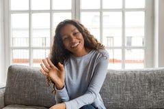 Szczęśliwa życzliwa amerykanin afrykańskiego pochodzenia kobiety falowania ręka patrzeje krzywka obraz royalty free