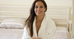 Szczęśliwa życzliwa młoda kobieta w białym kąpielowym kontuszu zbiory