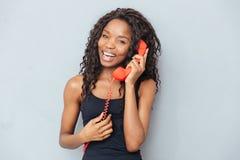 Szczęśliwa afro amerykańska kobieta opowiada na retro telefon tubce Zdjęcie Stock
