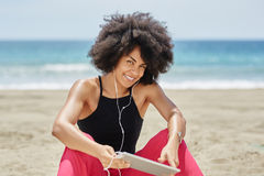 Szczęśliwa afro amerykańska kobieta relaksuje na plażowej słuchającej muzyce na t Zdjęcie Royalty Free