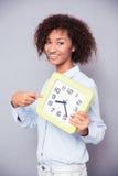 Szczęśliwa afro amerykańska kobiety pozycja z zegarem Obraz Stock