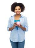 Szczęśliwa afro amerykańska młoda kobieta z prosiątko bankiem Zdjęcie Royalty Free