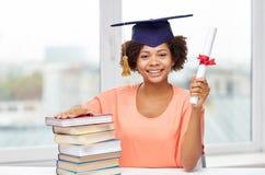 Szczęśliwa afrykańska kawaler dziewczyna z książkami i dyplomem zdjęcie royalty free