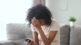 Szczęśliwa afrykańska kobieta patrzeje telefon śmia się przy śmiesznym dowcipem zbiory