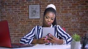 Szczęśliwa afrykańska kobieta swiping jej obsiadanie przed jej czerwonym laptopem w ceglanym pokoju i pastylkę