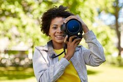 Szczęśliwa afrykańska kobieta z cyfrową kamerą w parku fotografia stock