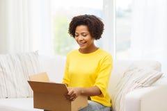Szczęśliwa afrykańska młoda kobieta z pakuneczka pudełkiem w domu Zdjęcie Royalty Free