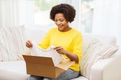 Szczęśliwa afrykańska młoda kobieta z pakuneczka pudełkiem w domu Zdjęcie Stock