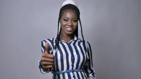 Szczęśliwa afrykańska uśmiechnięta dziewczyna pokazuje OK westchnienie przy kamerą podczas gdy stojący ovet szarość tło zbiory wideo