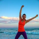 Szczęśliwa aktywna kobieta na seashore przy zmierzchu cieszeniem Zdjęcie Stock