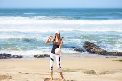 Szczęśliwa aktywna młoda kobieta na plażowej bawić się siatkówce Fotografia Stock