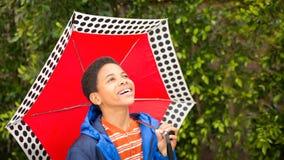 Szczęśliwa amerykanin afrykańskiego pochodzenia chłopiec śmia się, trzymający parasol i lookin zdjęcie royalty free