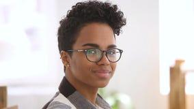 Szczęśliwa amerykanin afrykańskiego pochodzenia dziewczyna jest ubranym okulistycznych szkła patrzeje kamerę zbiory wideo