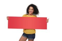 Szczęśliwa amerykanin afrykańskiego pochodzenia dziewczyna pokazuje pustego sztandar zdjęcia stock
