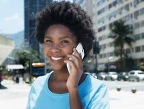 Szczęśliwa amerykanin afrykańskiego pochodzenia dziewczyna z telefonem komórkowym fotografia stock