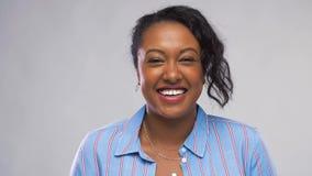 Szczęśliwa amerykanin afrykańskiego pochodzenia kobieta nad popielatym tłem zbiory