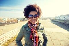 Szczęśliwa amerykanin afrykańskiego pochodzenia kobieta w cieniach na ulicie zdjęcia stock