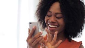 Szczęśliwa amerykanin afrykańskiego pochodzenia kobieta z smartphone zbiory