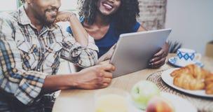 Szczęśliwa amerykanin afrykańskiego pochodzenia para ma śniadanie w ranku przy drewnianym stołem wpólnie Uśmiechnięty murzyn i je obraz royalty free