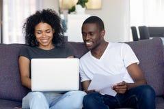 Szczęśliwa amerykanin afrykańskiego pochodzenia para używa laptop, otrzymywa dobre wieści zdjęcie stock