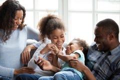 Szczęśliwa amerykanin afrykańskiego pochodzenia rodzina bawić się z dziećmi w domu obrazy royalty free