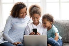 Szczęśliwa amerykanin afrykańskiego pochodzenia rodzina używa urządzenia przenośne wpólnie zdjęcia stock