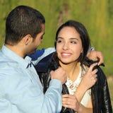 Szczęśliwa arabska para flirtuje podczas gdy mężczyzna pokrywa z jego kurtką w parku ona fotografia stock